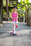 Asian little Chinese girl playing with scooter Stock Photos