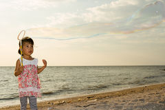 Asian Little Chinese Girl Playing Soap Bubbles on the Beach Royalty Free Stock Photo