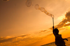 Asian Little Chinese Girl Playing Soap Bubbles on the Beach Stock Photo