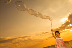 Asian Little Chinese Girl Playing Soap Bubbles on the Beach Royalty Free Stock Image