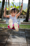 Asian little Chinese girl playing swing. At outdoor park Royalty Free Stock Photos