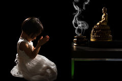 Asian Little Chinese Girl Praying in front of Buddha. In isolated Black Background Royalty Free Stock Photos