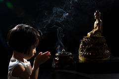 Asian Little Chinese Girl Praying in front of Buddha. In isolated Black Background Stock Images