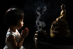 Asian Little Chinese Girl Praying in front of Buddha. In isolated Black Background Stock Photos