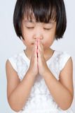 Asian Little Chinese Girl Praying. In isolated White Background Stock Photo