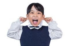 Asian Little Chinese Girl pulling ears and making a grimace Stock Photos