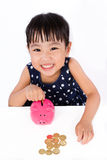 Asian Little Chinese Girl Putting Coins Into Piggy Bank Stock Images