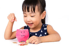 Asian Little Chinese Girl Putting Coins into Piggy Bank Royalty Free Stock Image