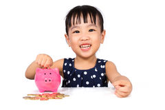 Asian Little Chinese Girl Putting Coins into Piggy Bank Stock Photography