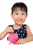 Asian Little Chinese Girl Putting Coins into Piggy Bank Stock Photo