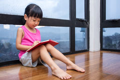 Asian little Chinese girl reading a book near the window. At home Stock Photos