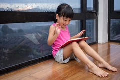 Asian little Chinese girl reading a book near the window. At home Stock Photography