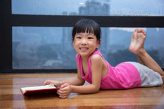Asian little Chinese girl reading a book near the window. At home Royalty Free Stock Photo