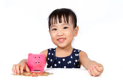 Asian Little Chinese Girl Saving Money in a Piggy Bank Royalty Free Stock Photography