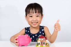 Asian Little Chinese Girl Saving Money for Property Concept Stock Photos