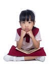 Asian Little Chinese girl sitting on floor and reading book Stock Photo