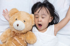 Asian little Chinese girl sleeping with teddy bear. On the bed at home Royalty Free Stock Photos