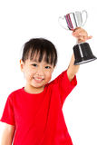 Asian Little Chinese Girl Smiles with a Trophy in Her Hands. Isolated on White Background royalty free stock image