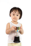Asian Little Chinese Girl Smiles with a Trophy in Her Hands. Isolated on White Background royalty free stock photography
