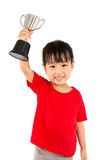 Asian Little Chinese Girl Smiles with a Trophy in Her Hands. Isolated on White Background stock photography