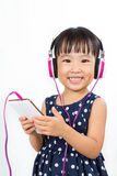 Asian Little Chinese Girl Using Mobile Phone with Headset Stock Photo