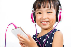 Asian Little Chinese Girl Using Mobile Phone with Headset Royalty Free Stock Photography