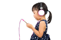 Asian Little Chinese Girl Using Mobile Phone with Headset Stock Images