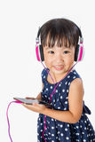 Asian Little Chinese Girl Using Mobile Phone with Headset Royalty Free Stock Photos