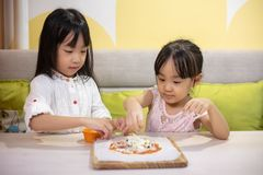 Asian Little Chinese Girls DIY mini pizza. At home stock photography