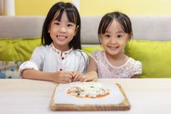Asian Little Chinese Girls DIY mini pizza. At home stock images