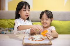 Asian Little Chinese Girls DIY mini pizza. At home royalty free stock photos