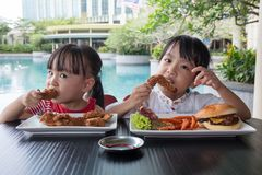 Asian Little Chinese Girls Eating Burger and Fried chicken. At Outdoor Cafe Stock Photos