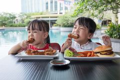 Asian Little Chinese Girls Eating Burger and Fried chicken. At Outdoor Cafe Royalty Free Stock Images