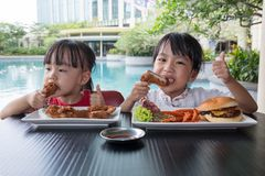 Asian Little Chinese Girls Eating Burger and Fried chicken. At Outdoor Cafe Stock Photo