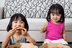 Asian Little Chinese Girls Eating Pizza. At Home royalty free stock photography