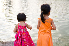 Asian Little Chinese Girls Feeding Fish Stock Photography