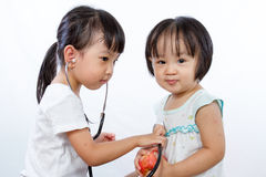 Asian Little Chinese Girls Playing as Doctor and Patient with St. Ethoscope on white background stock image