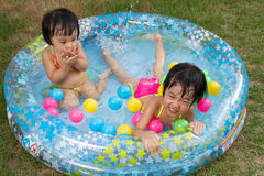 Asian Little Chinese Girls Playing in an Inflatable Rubber Swimm Stock Photo