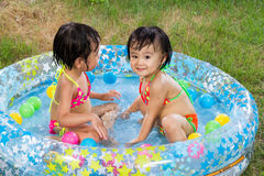 Asian Little Chinese Girls Playing in an Inflatable Rubber Swimm Royalty Free Stock Photo