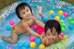 Asian Little Chinese Girls Playing in an Inflatable Rubber Swimm Royalty Free Stock Photography