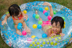 Asian Little Chinese Girls Playing in an Inflatable Rubber Swimm Royalty Free Stock Photos