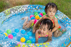 Asian Little Chinese Girls Playing in an Inflatable Rubber Swimm Stock Image