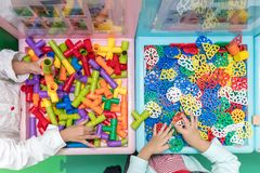 Asian Little Chinese Girls playing puzzle. At Indoor Playground Stock Photos