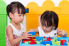 Asian Little Chinese Girls Playing Wooden Blocks. At Home or Kindergarten stock images