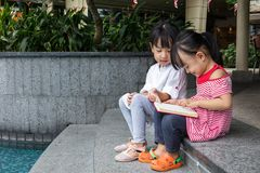 Asian Little Chinese Girls reading a book. Beside the fountain outdoor Stock Image