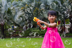 Asian Little Chinese Girls Shooting Bubbles from Bubble Blower Royalty Free Stock Image