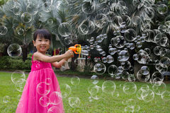 Asian Little Chinese Girls Shooting Bubbles from Bubble Blower Stock Images