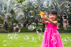 Asian Little Chinese Girls Shooting Bubbles from Bubble Blower Royalty Free Stock Photos