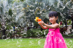 Asian Little Chinese Girls Shooting Bubbles from Bubble Blower Stock Photos
