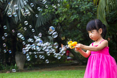 Asian Little Chinese Girls Shooting Bubbles from Bubble Blower. In the Park Stock Images